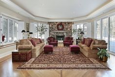 Large living room wing with windows on 3 sides of the room.  Large sitting area on rug on top of wood floor.  Large stone fireplace at end of room surrounded by windows.