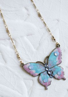 "Sweet Parpalla Indie Necklace 33.99 at shopruche.com. This charming necklace features a pink and blue butterfly pendant adorned with light purple jewels. Hangs from a gold colored chain., ,  18"" long,  Pendant: 1.75"" wide"