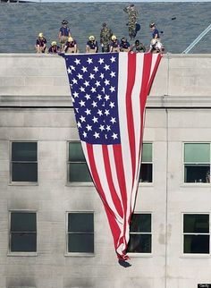 Firefighters and soldiers unfurl an American flag from the roof of the damaged side of the Pentagon on September 12th, 2001. AFP PHOTO/Luke FRAZZA (Photo credit should read LUKE FRAZZA/AFP/Getty Images)