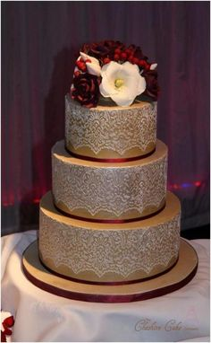 """""""Lace and Antique Gold"""" wedding cake ~ iced in an antique gold colour and then white lace stencilled on top. The posy of sugar flowers on top was made to  look like the bride's bouquet of burgundy roses, ivory Lissianthus and red hypernicum berries. ~ all edible"""