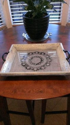 Old frame painted and antiqued. Added gray burlap with black paint doillie painted on and attached black handles. Cute little bedside tray. #diy #repurposed