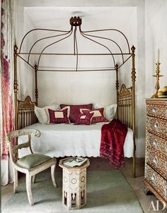 In the bedroom of a riad in Marrakech, an antique Spanish bed is livened up with embroidered pillows from Fez and Rabat | archdigest.com