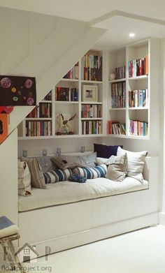 Adorable use of the space under the stairs! Reading nook with bench. Kids would love this!