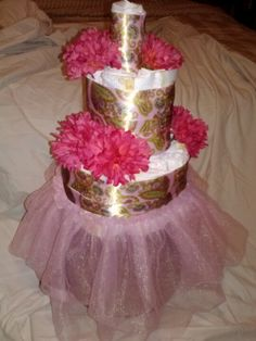 Easy diaper cake. 1.Roll 11 diapers bottom to top and tie with yarn. Take diapers in a circle around a bottle. Put ribbon around bottom layer.  2. Roll & tie 6 diapers and tape in a circle around the top of the bottle to make the 2nd layer. Wrap ribbon around this layer. 3. Roll 1 diaper and tape ribbon around this diaper.  4. I just put a dress up tutu along the bottom layer and it can sit on a cake stand. 5. The last thing I did was buy $1 fake  flowers from Walmart and took them off the…