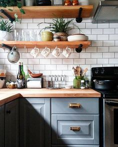 Open shelves make even the smallest of kitchens feel open and airy! Love the brass handles and cabinet color.