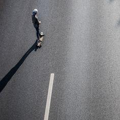 rollt 02 – Auf dem Highway Richtung Sonne. Schräges Licht, immer geradeaus. Die Figuren wie freigestellt auf Asphalt. 2014, MD | © www.piqt.de | #PIQT
