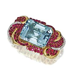 AQUAMARINE, RUBY AND DIAMOND PENDANT-BROOCH, CIRCA 1950 The emerald-cut aquamarine weighing approximately 46.75 carats, within a stylized scrollwork frame set with round and calibré-cut rubies and single-cut diamonds, mounted in 18 karat gold.