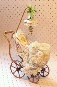 Jill Dianne - antique style Pink Mechanical Fairy Buggy - Dollhouse Miniatures  Hand-painted tapestry rose pillow.  Pink velveteen bedding.  Hand-tinted pink lace flower baby throw with embroidered French knots.  Hand-painted wire wicker buggy.  Painted silver-based mechanical fairy with sculpted clay wings,  dangling under a sculpted flower umbrella with lace and silk ribbon. 335 USD.