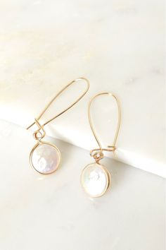 Melted Pearl Drop Earrings A simple yet sophisticated pair of golden wire drop earrings that secure by a hook and wire closure on back and feature a melted pearl detail on the end.
