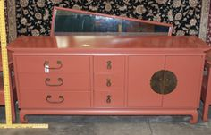 VINTAGE MID CENTURY MODERN KENT COFFEY AMERASIA SALMON COLORED CREDENZA DRESSER BUFFET. ACCOMPANYING THIS PIECE IS A 32X56 INCH MIRROR THAT IS MEANT TO BE HUNG ON A WALL. FEATURES A TOTAL OF 9 DRAWERS, WITH THREE BEING HIDDEN BEHIND TWO DOORS. CREDENZA HAS A PAGODA STYLE TOP WHICH CURLS UP AT THE ENDS AND CURVED FEET. BRASS CHINOISERIE HARDWARE AND DOVETAIL JOINERY FINISHES OFF THIS PIECE. OVERALL GOOD, CLEAN CONDITION BUT MINUTE PAINT LOSS IS VISIBLE. BURNED MAKERS MARK IN TOP LEFT DRAWER…