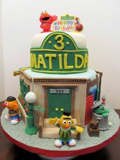"""Sesame Street cake for my granddaughter's 3rd birthday.  8"""" hexagon for bottom tier and 6"""" round for top tier.  Cake is vanilla with red, green, yellow & blue polka dots inside!  We of course have Bert and Ernie house at 123 Sesame Street, Mr. Hooper's Store, Oscar the Grouch, Big Bird and I put a Pet Shop on Sesame Street because I wanted to use my new doggie molds!  My granddaughter was excited for the whole week before her birthday watching me make all the parts!   I had so much fun making th"""