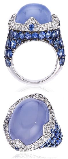 A chalcedony, sapphire and diamond ring, Asprey,  centering a blue chalcedony cabochon measuring approximately 19.80 x 14.70 x 10.30mm., surrounded by round brilliant-cut diamonds, further accentuated by oval and circular-cut blue sapphires; signed Asprey, with signed pouch; blue chalcedony weighing approximately: 22.40 carats; estimated total sapphire weight: 8.90 carats; mounted in eighteen karat white gold; size 5 3/4. Via Bonhams.