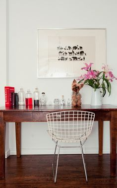 Great use of the Bertoia chair. Simple print, rich wood, pop of colour from the flowers, vintage apothecary bottles.
