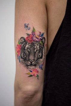 Beautiful arm tattoo depicting a tiger's head which is decorated with some nice flowers!