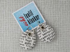 Type, letter, font and words in black and white for your ears.  The accurately hand-sewn pendants (2,6 cm x 3,2 cm / 1.02 inch x 1.26 inch) are added to silver hoops (diameter: 1,6 cm / 0.63 inch, 935 silver).  The fabric of the earrings was part of a vintage handkerchief, showing the description of a female and a male Aquarius (see last foto).  The earrings are double-sided: if you like a change, just turn the other side of the pendants to the front