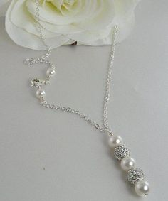 This simple yet elegant bridal necklace, made with a glimmering pave crystal and white Swarovski pearl pendant suspended on lovely sterling silver chain, is ...
