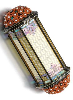 Superb gem set vanity case, Cartier, 1925. The octagonal gold box decorated with white enamel wave motifs, mother-of-pearl inlay, and black enamel, the terminals covered in carved coral flowers, seed pearls, cabochon emeralds, and circular-, single-cut and rose diamonds, signed Cartier, numbered, French assay and maker's marks. #Cartier #ArtDeco #vanity
