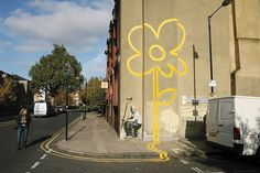 """In London, a stenciled worker transmutes the no-parking lines he is painting into a stylized flower."" -by Banksy"