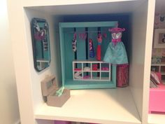 Sage's Dreamhouse. This is the closet.  Wood crate is spray painted, and I added hooks to hold a spoke for the rod. Mirror is from michaels with a hand made sewn bunting. Wood box is painted for accessories. Hangers were ordered from amazon.  Sage Leaf Studio 2013.