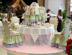 THE ENCHANTED BABY SHOWER The Enchanted Baby, Inc. Celebrating a bundle of joy, this table captures whimsical storybook charm. Mixing prints, dotted Swiss, organza ribbons and tassels spun through gathers, ruffles and tufts, it features a scaled, fully dressed baby crib nestled high aloft as its centerpiece.