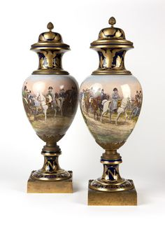 A pair of Mounted Sevres Style Napoleonic Lidded Urns. Late 19th century, with red overglaze Sevres mark and date mark for 1804, the base dated ''1806''; the second: the base dated ''1805'', each gilt bronze-mounted, with a pinecone-form finial atop a domed gilt-painted cobalt ground lid and collar, the oviform body painted with a continuous scene of Napoleon on horseback.  by his troops, over a stepped socle above a spreading gilt-painted base, raised overall on a beaded square plinth.