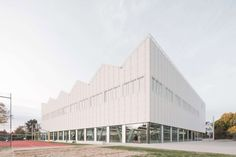 The studio wrapped the sports centre in an expanded-metal lattice shell to create a light and airy design. Metal Facade, Metal Buildings, Concrete Cover, Metal Lattice, Masterplan, Concrete Staircase, Glazed Walls, Expanded Metal, Exposed Concrete
