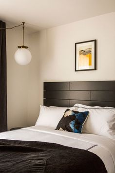 Round hanging light and framed art above black and white bedding.