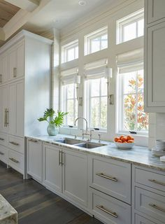 The light gray kitchen cabinets are adorned with extra long satin nickel pulls. A stainless steel dual kitchen sink stands under a row of windows dressed in white roman shades illuminated by Ruhlmann Single Sconces.