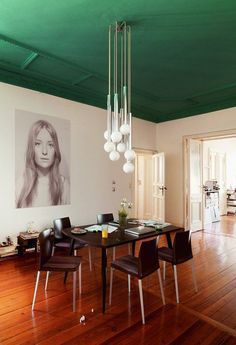 Stunning green ceiling, art work, and chandelier. Definitely want to eat dinner in here!