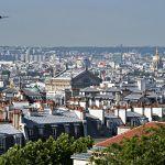 Paris vu depuis le Sacré-Cœur, au premier plans les toits et leur petites cheminées rouge brique et à l'horizon le ciel pollué.