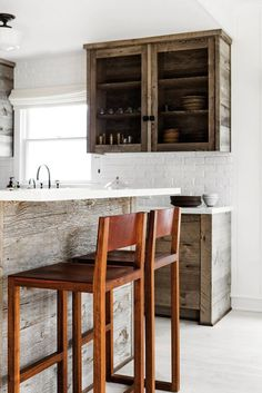 Stools made of black walnut and leather by BDDW add an organic note to the pared-down dining area.
