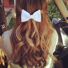 Pull a strand of hair from each side of head, attach together with a bow! Super cute!