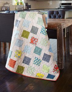 This quilt design provides a good place to showcase your favorite prints. The quilt appears to be randomly arranged squares, but there's a method to the construction. Learn how to make Tossed Squares in our free video tutorial.