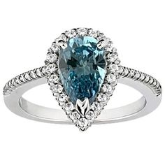 Here's a mesmerizing design on this unique shank that comes with this 14k White Gold Pear Shape Halo Blue Diamond Engagement Ring placed within a Prong setting featuring a Blue Pear Cut center stone along with White Round Brilliant cut accent side stones on the top of the Halo style mount. The Pear Shape Halo …