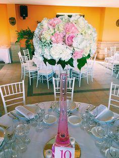 Centro de mesa en cristal alto, con rosas, hortensias y enredadera.
