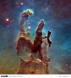 """Mistik Dağ: Yıldızların Doğuşu """"Yaradılış Sütunları""""  Hubble Uzay Teleskobu'nun çektiği en etkileyici fotoğraflar arasında yer alan """"Yaratılış Sütunları"""" 20. yılı şerefine 2014'de bir kez daha görüntüledi. Dünyaya 7 bin ışık yılı uzaklıktaki toz ve gaz sütunlarını temsil eden bu kozmik yapı, yıldız doğum fabrikası olarak tanımlanıyor. Bu fotoğraf Hubble tarafından 2014 yılında çekilmiştir."""