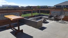 Outdoor entertainment area, gabion / glass winder breaker. Paved seating area with fire pit. Macrocarpa bar leaner