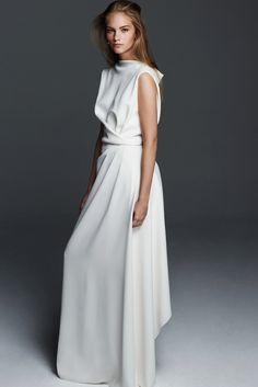 TIMO, long sleeveless dress in milk-white cady, unique for its elegant draping and dipped hem that play with roomy and tight-fitting volumes. A contemporary style that highlights harmonious and sinuous lines. #maxmarabridal #weddingdress #wedding