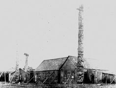 The Halibut House is shown here with it's frontal pole before the pole was shipped to Jasper, BC. Notice the support posts angled along the side of the walls of the houses. In the background is the Star House.