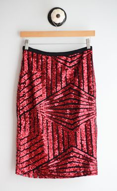"Geometric pencil skirt with red sequins, fully lined and midi length. Elastic waistband. Fits true to size. 95% Polyester, 5% Spandex Waist: Small 28"", Medium 30"", Large 32"" Length: Small 24"", Medium"