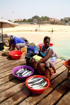 Woman selling fish with her baby at the fishmarket, Santa Maria harbour, Sal, Cape Verde
