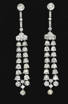A PAIR OF BELLE EPOQUE DIAMOND EAR PENDANTS, BY CARTIER   Each bezel-set with an old European-cut diamond, suspending a line of collet-set and single-cut diamonds, to an old European-cut diamond plaque, suspending a graduated double-row old mine-cut diamond tassel each within a tulip-shaped surround, with old European-cut diamond drops, mounted in platinum, circa 1905, in their original Cartier red leather fitted case  Signed Cartier, no. 6030 (indistinct)