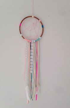 Wall hanging / dream catcher that will look cute in any room or nursery. 8 inch (21cms) hoop with a mixture of ribbons, lace, a bell, and feathers. From top of the hoop to the bottom of longest feather approximately 65-75cms.Very eye catching and will create a talking point in the room. Please note:: this dream catcher is made to order and will not look exactly the same as the picture. Some ribbons may slightly differ and the placement may differ slightly. PLEASE ALLOW ...