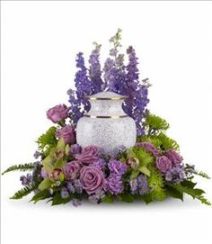 Soft lavender and green blooms to surround the urn, like a peaceful, contemplative garden. <br><br>A subdued assortment of flowers such as lavender larkspur, roses and asters are grouped beautifully with the rich greens of cymbidium orchids, chrysanthemums, English boxwood and sword fern. Approximately 23 1/2' W x 20' H.