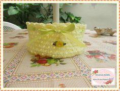 Cesta tejida a crochet, en lana amarilla, adornada con un lazo de cinta y una florcita de tela. Tejido endurecido con almidón.