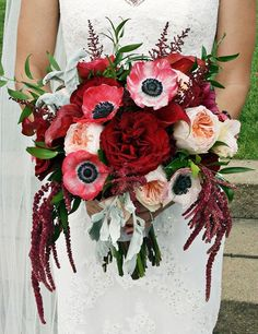 Deep red and pink garden roses with red anemones & amaranthus make a striking bouquet.