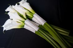 Calla Lilly Bouquets for bridesmaids. I am thinking they will hold three that have sleek black ribbon