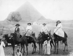 c.1900. Tourists brave the heat in long skirts, jackets and hats while sitting atop camels attended to by locals. In the background of this shot from 1900 is the pyramid and sphinx at Giza.