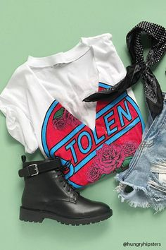 """A relaxed, slub knit tee featuring a """"Stolen"""" graphic with roses on the front, a raw V-cut out, choker neck design, and short sleeves."""