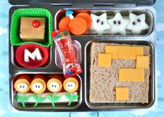 Power Up lunch is packed in her PlanetBox & contains:  Cherry tomato, cheddar & mozzarella Fire Flowers  Galia melon initial M for Mario  Fig Newtons with a bento pick Super Mushroom  Carrot Coins (& another mushroom bento pick)  Galia melon Stars with chocolate chip sliver eyes  Turkey & cheese Mystery Block sandwich  A Super Mario gummy fruit candy treat